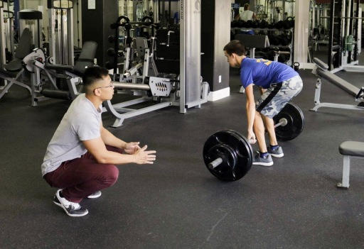 Certified Personal Trainer, Vincet, observes Tanner perform a deadlift.